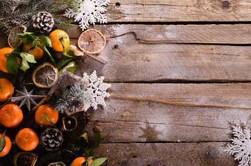 Magic Christmas background - vintage wood, candy cane, house, cinnamon, star anise, sweet mandarins with green leaves, cones, snowflakes. New Year. Top view, blank space