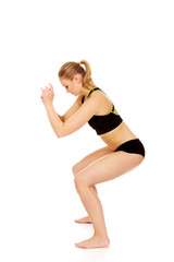 Young athletic woman performs squats
