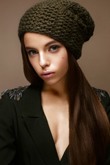 Beautiful girl in winter knit hat and khaki jacket. Young model with gentle makeup and colored arrows on her eyes. Warm winter picture. Beauty face.