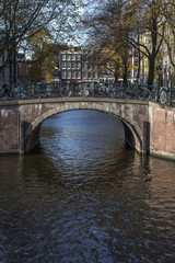 Old brown bridge with bikes over the canal in autumn in the day in Amsterdam