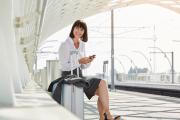 traveling business woman with smart phone and luggage
