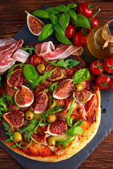 Fig pizza with bacon, green pimiento olives, rocket and basil leaves