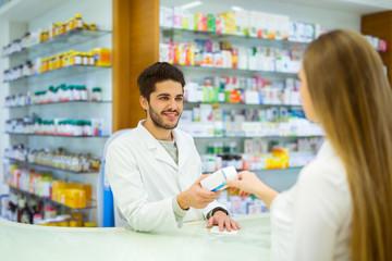 Experienced pharmacist counseling female customer in modern pharmacy