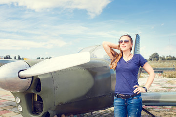 Young happy woman standing near sport plane on airfield delighted before flight.