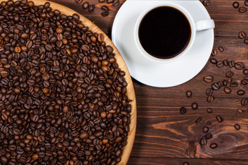 cup of coffee and coffee beans on a wooden table. Horizontal top view
