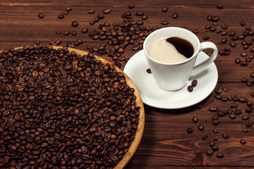 A cup of coffee on a wooden table. Coffee beans in a large dish.