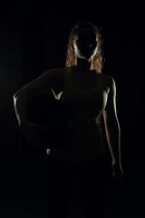 Young woman stands with the ball backlight and shadow in gym