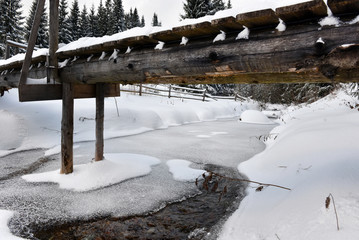 Small water stream, river covered with snow