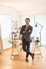 Looking at camera, young architect standing in front of his desk