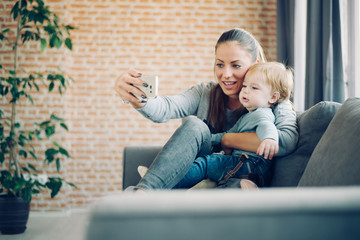Mom and toddler taking selfie in cosy living room