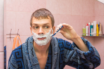 Young man shaves the stubble on his cheek