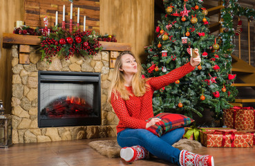Young woman in country house sitting on the floor, nearly fireplace and give a kiss on mobile. Merry Christmas concept.