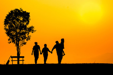 silhouette family over grass background at sunset