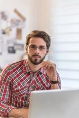 Looking at camera a young man sitting at his desk