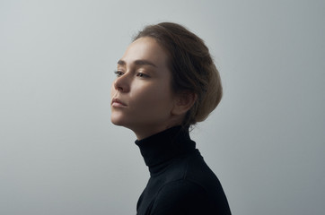 Dramatic portrait of a young beautiful girl with freckles in a black turtleneck on white background in studio Wall mural