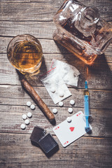 Hard drugs and alcohol on an old wooden table. Top view