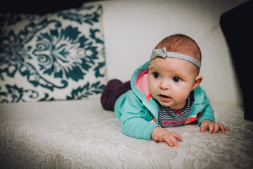 Baby girl plays on the couch at home. Baby newborn attentively looks.