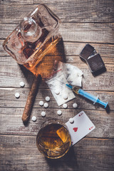 Hard drugs and alcohol on an old wooden table