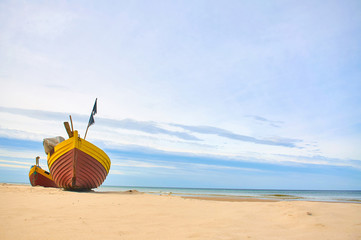 Fishing boat at baltic sea sandy beach with dramatic sky during summertime in Poland Wall mural