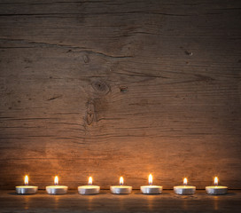 burning candles on the background of old barn boards