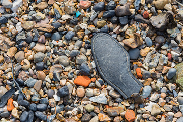 Pebble beach with a part of an old shoe