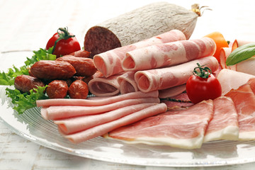 Food tray with delicious salami, pieces of sliced ham, sausage, tomatoes, salad and vegetable - Meat platter with selection - Cutting sausage and cured meat on a celebratory table.