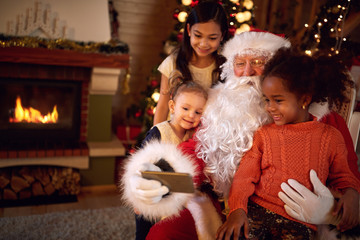 Santa Claus taking selfie during Christmas atmosphere with child