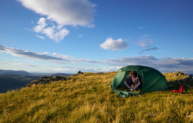 A hiker camping on the mountain summit of Place Fell in the Lake