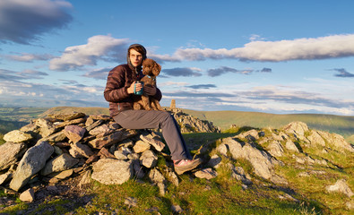 A hiker enjoying a hot drink with their dog on the summit of Place fell, English Lake District. UK.