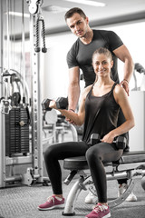 Woman doing bicep curls in gym with her personal trainer