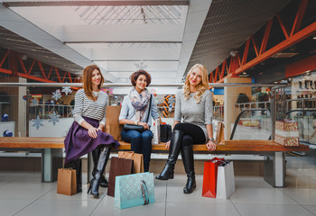 Three girls sitting in shopping mall and looking at the camera