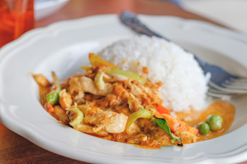 Thai cuisine, chicken curry closeup with rice on the blurred cafe background.