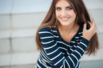 Portrait of a happy  woman with long straight hair and gray-green eyes,nice smile,white straight teeth,dressed in a dark pullover with white stripes posing on a city street,sitting on the steps