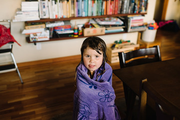 Portrait of girl at home, wrapped in bath towel, with wet hair