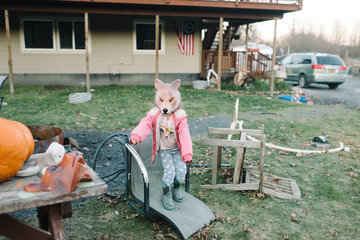 Portrait of girl wearing fox mask, standing in yard