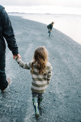 Father and daughter, walking on beach, holding hands, rear view