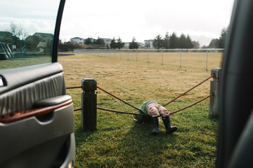 Girl balancing on rope fence beside parked car