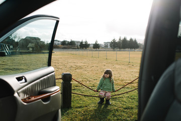 Girl sitting on rope fence, beside parked car