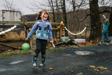 Girl playing outdoors, with mud on face, laughing