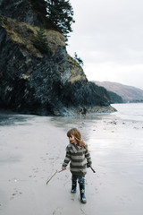 Girl walking on beach, holding stick