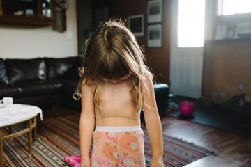 Girl standing in living room, semi dressed