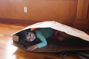 Girl lying in cardboard box, smiling