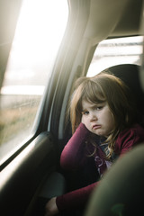 Portrait of girl, sitting in back seat of car, grumpy expression