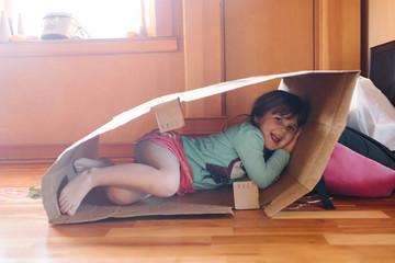 Portrait of girl lying in cardboard box, smiling