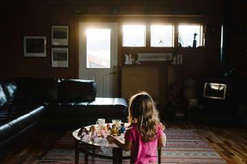 Young girl playing with dolls in living room, rear view