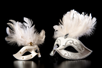 Pretty white venician golden carnival masks with feathers on a mysterious black background