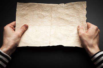 Strong sailor hands hold empty old map