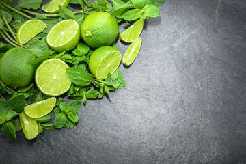 Limes and mint on stone background. Top view with copy space