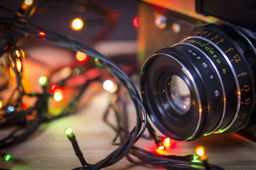 Vintage camera lens with garland christmas lights on colorful bokeh background. Mockup for holiday new year greeting card