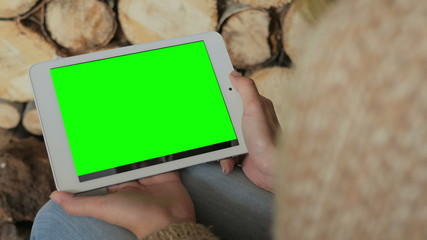 Woman looking at horizontal tablet computer with green screen. Close up shot of woman's hands with pad